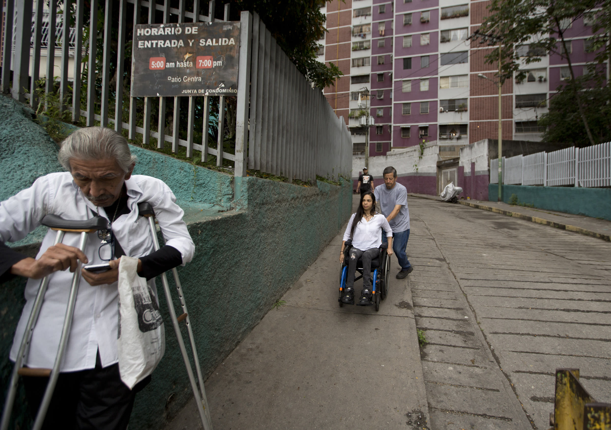 In this Dec. 17, 2018 photo, neighbor Dixon Rosales helps dancer Iraly Yanez negotiate her wheelchair on a downhill path, in Caracas, Venezuela. A stray bullet crushed Yanez's aspirations of becoming a professional dancer eight years ago as it ruptured two of her vertebrae and left her paraplegic. (AP Photo/Fernando Llano)