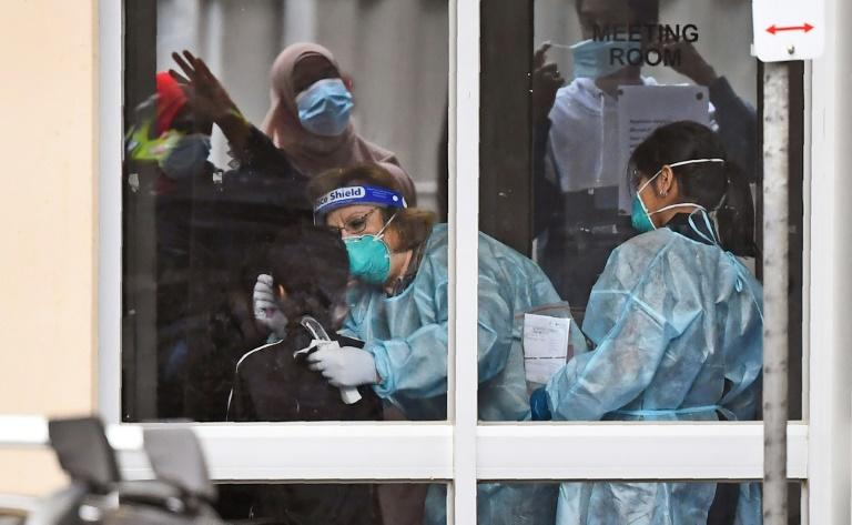 Medical staff perform a COVID-19 coronavirus test on a resident of one of nine public housing estates locked down due a spike in infection numbers in Melbourne (AFP Photo/William WEST)