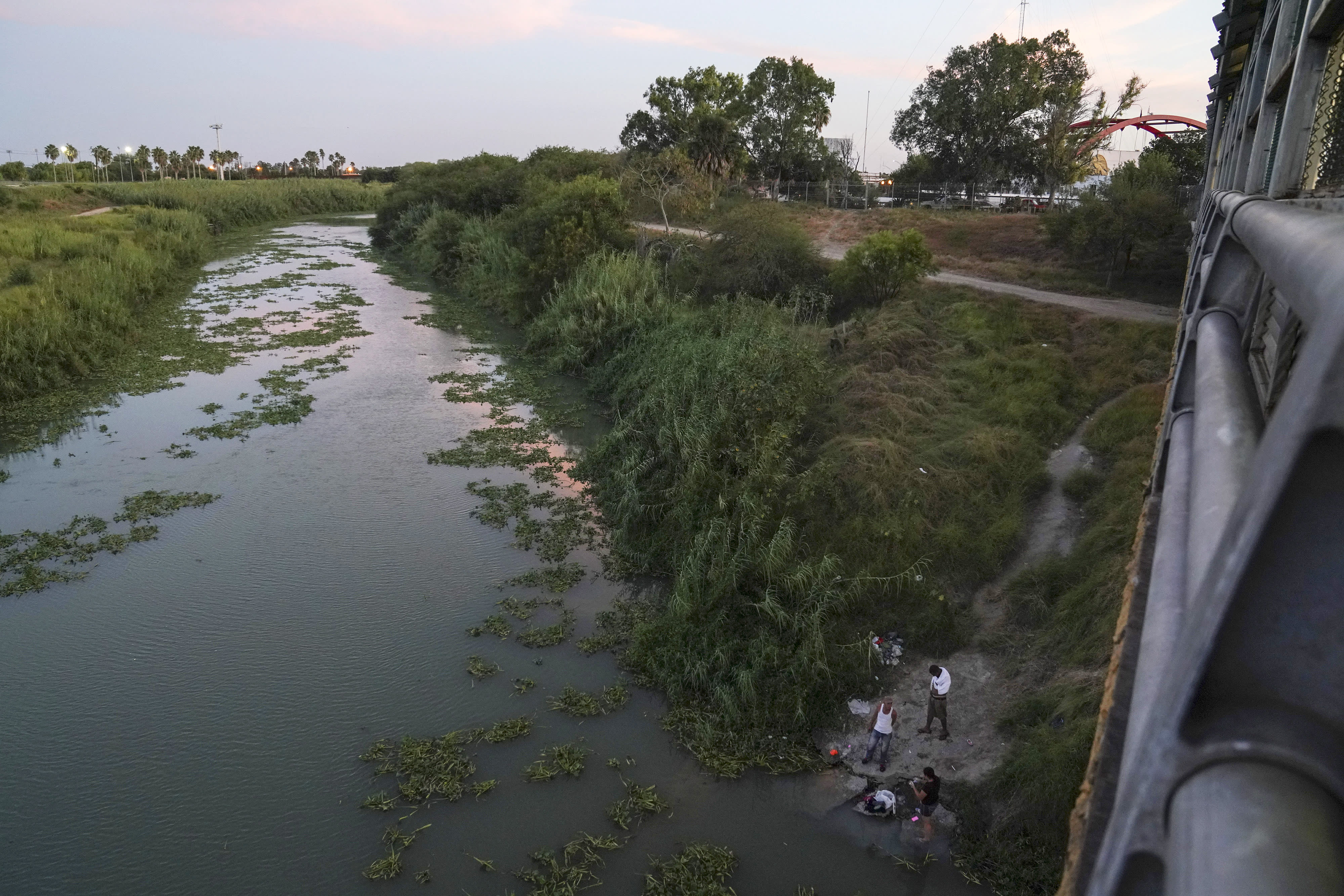 """In this Aug. 30, 2019, photo, asylum seekers from Cuba and Nicaragua wash their clothes in the Rio Grande near the Gateway International Bridge in Matamoros, Mexico. They were sent back to Mexico to wait for their asylum case under the """"Remain in Mexico"""" program, officially called the Migrant Protection Protocols. (AP Photo/Veronica G. Cardenas)"""