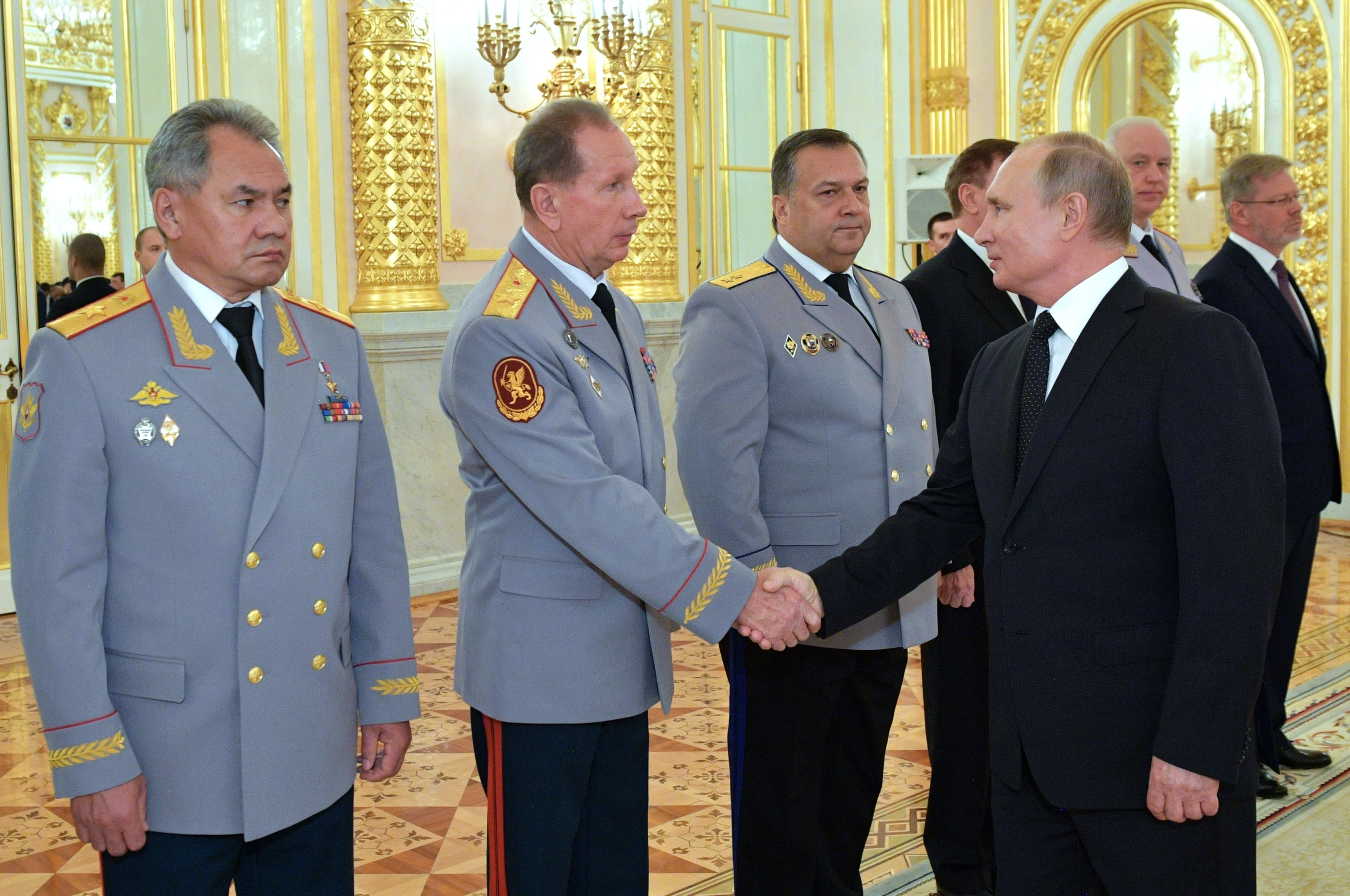 Russian President Vladimir Putin, right, greets Commander-in-Chief of the National Guard troops Viktor Zolotov, second left, Defense Minister Sergei Shoigu, left, and Director of the Federal Security Service Dmitry Kochnev, right, during a meeting with top military officers and law enforcement officials in the Kremlin in Moscow, Russia, Thursday, Oct. 25, 2018. Putin said that Russia has adhered to its obligations in the arms control sphere, but noted that Russian arsenals will be modernized to ensure protection from any potential threats. (Alexei Nikolsky, Sputnik, Kremlin Pool Photo via AP)