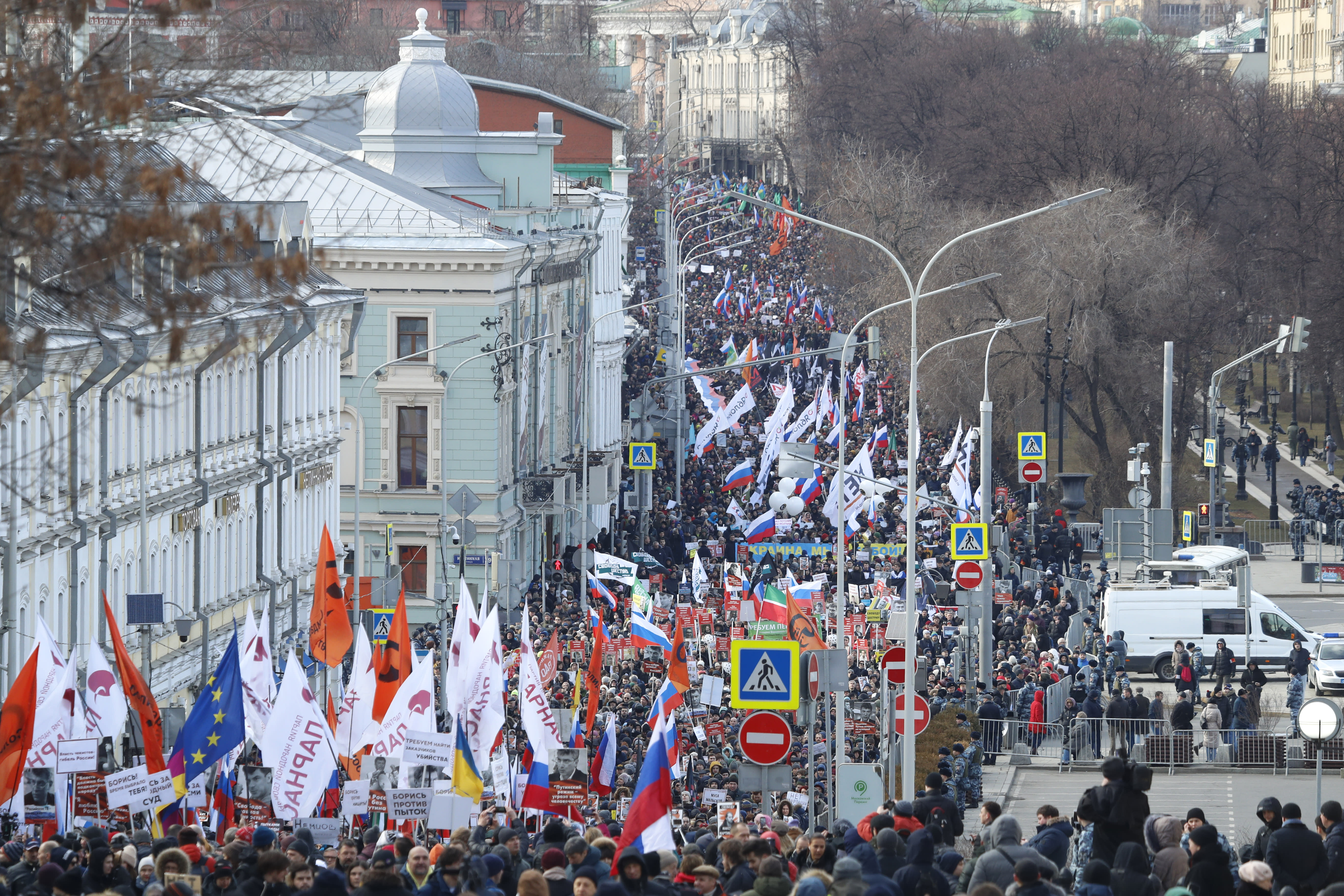 Demonstrators, with flags of different opposition movements, march in memory of opposition leader Boris Nemtsov in Moscow, Russia, Saturday, Feb. 29, 2020. Nemtsov, a charismatic Russian opposition leader and sharp critic of President Vladimir Putin, was gunned down on Feb. 27, 2015 near the Kremlin in Moscow, Russia. (AP Photo/Pavel Golovkin)