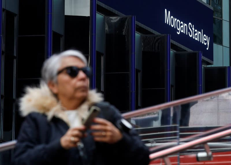 A woman takes photos by the Morgan Stanley building in Times Square in New York