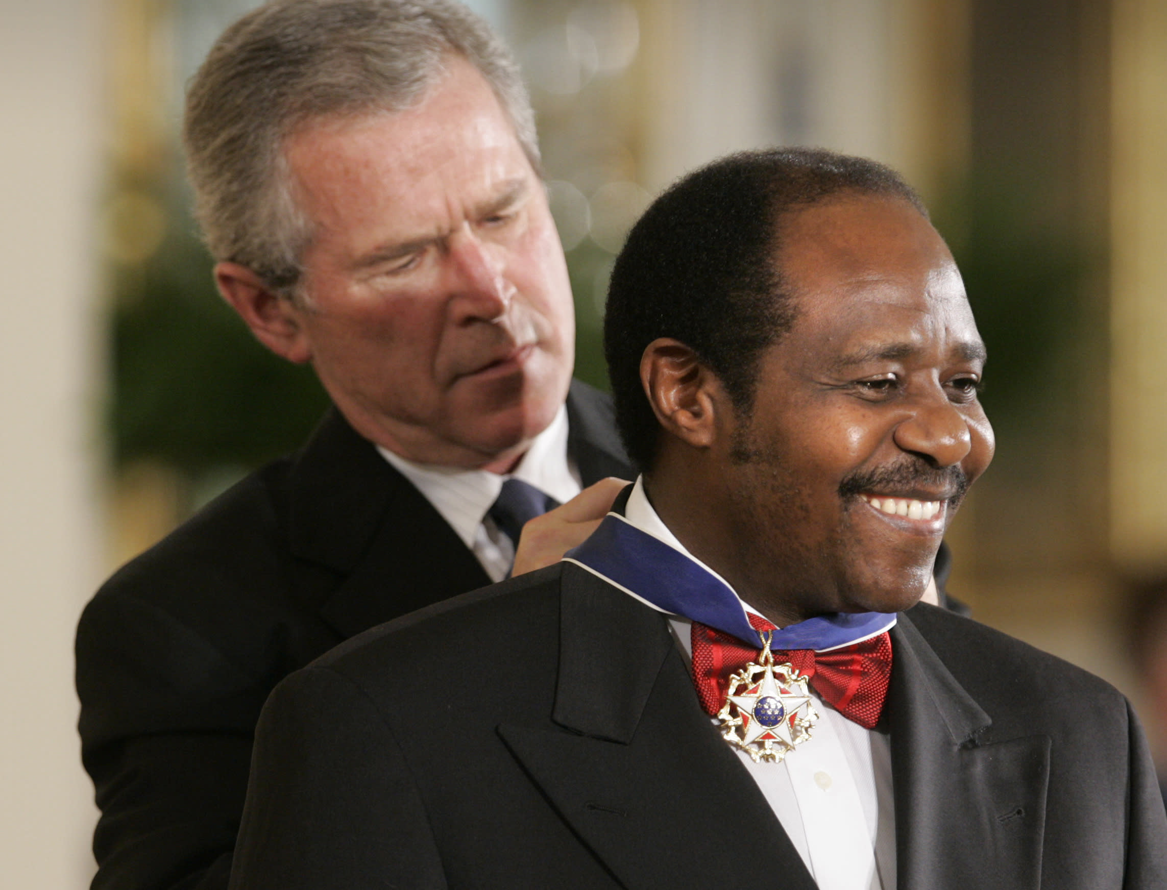 """FILE - In this Wednesday, Nov. 9, 2005 file photo, President Bush awards Paul Rusesabagina, who sheltered people at a hotel he managed during the 1994 Rwandan genocide, the Presidential Medal of Freedom Award in the East Room of the White House, in Washington. Rusesabagina, who was portrayed in the film """"Hotel Rwanda"""" as a hero who saved the lives of more than 1,200 people from the country's 1994 genocide, and is a well-known critic of President Paul Kagame, has been arrested by the Rwandan government on terror charges, police announced on Monday, Aug. 31, 2020. (AP Photo/Lawrence Jackson, File)"""