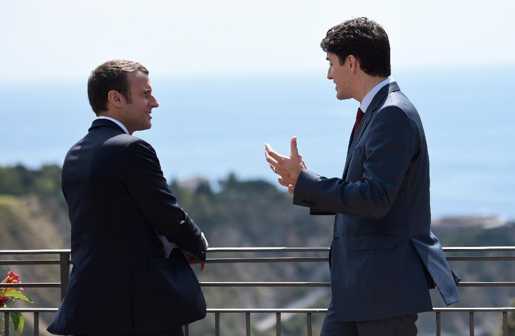 Canadian Prime Minister Justin Trudeau (R) and French President Emmanuel Macron chatted against the backdrop of a sparkling blue Mediterranean sea (AFP Photo/STEPHANE DE SAKUTIN)