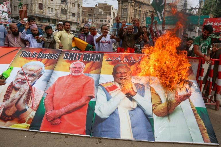 Protesters burn pictures of Indian Prime Minister Narendra Modi during a protest in Hyderabad after India stripped Kashmir of its autonomy: the UN Security Council is to hold a rare meeting on the Himalayan region on Friday
