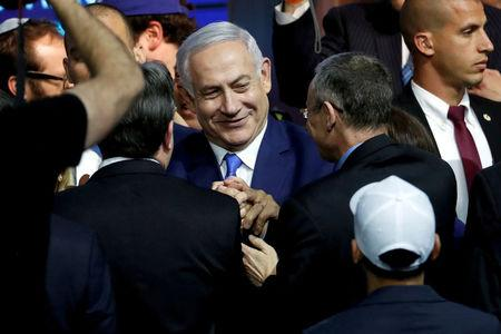 FILE PHOTO: Israeli Prime Minister Benjamin Netanyahu is greeted by supporters of his Likud party as he arrives to speak following the announcement of exit polls in Israel's parliamentary election at the party headquarters in Tel Aviv, Israel