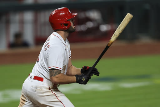 Cincinnati Reds' Mike Moustakas watches his three-run home run in the eighth inning during a baseball game against the Milwaukee Brewers in Cincinnati, Monday, Sept. 21, 2020. (AP Photo/Aaron Doster)