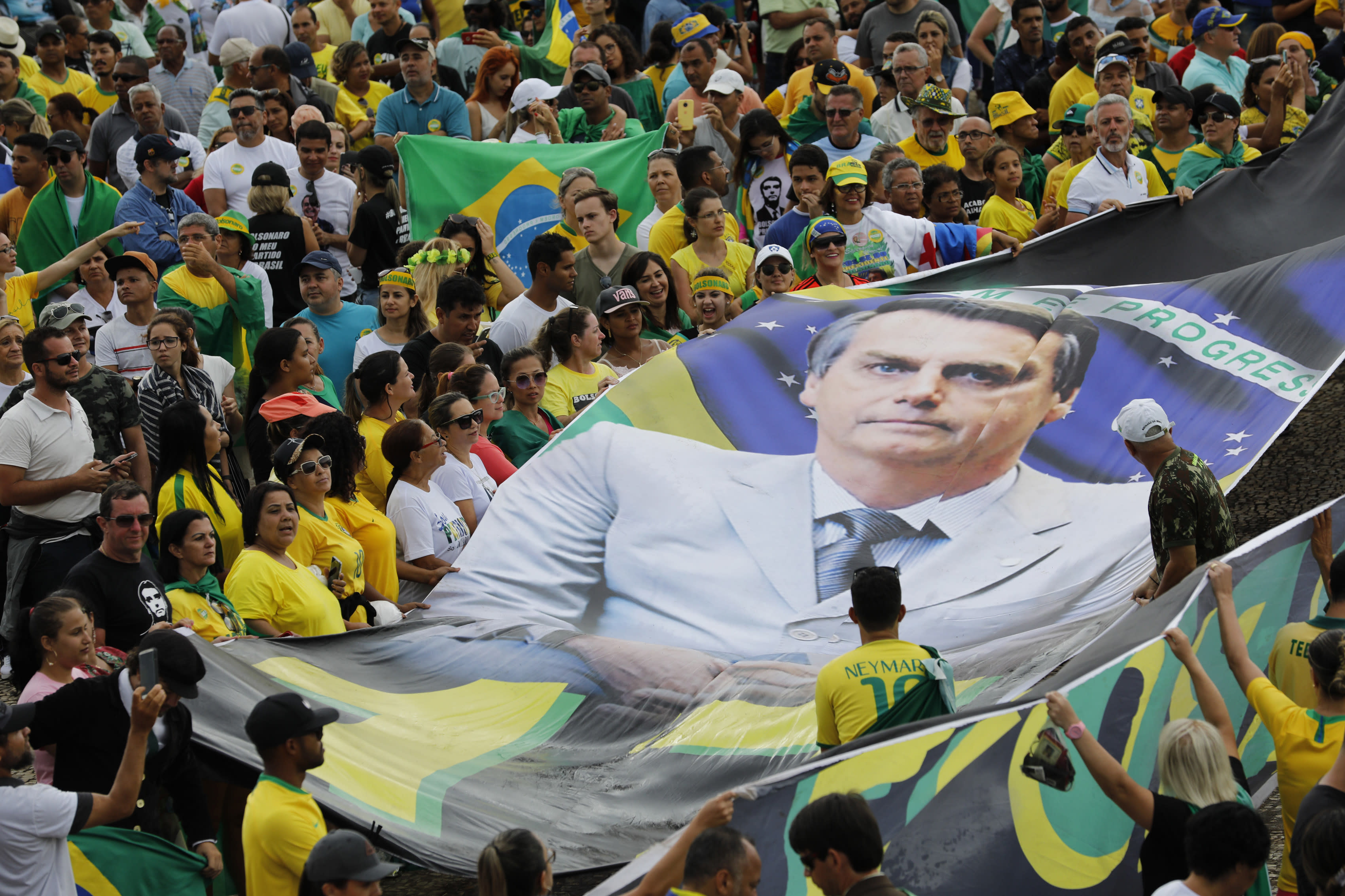 In this Tuesday, Jan. 1, 2019 photo, supporters of Brazil's new President Jair Bolsonaro display a giant banner of him on his inauguration day in Brasilia, Brazil. (AP Photo/Silvia Izquierdo)