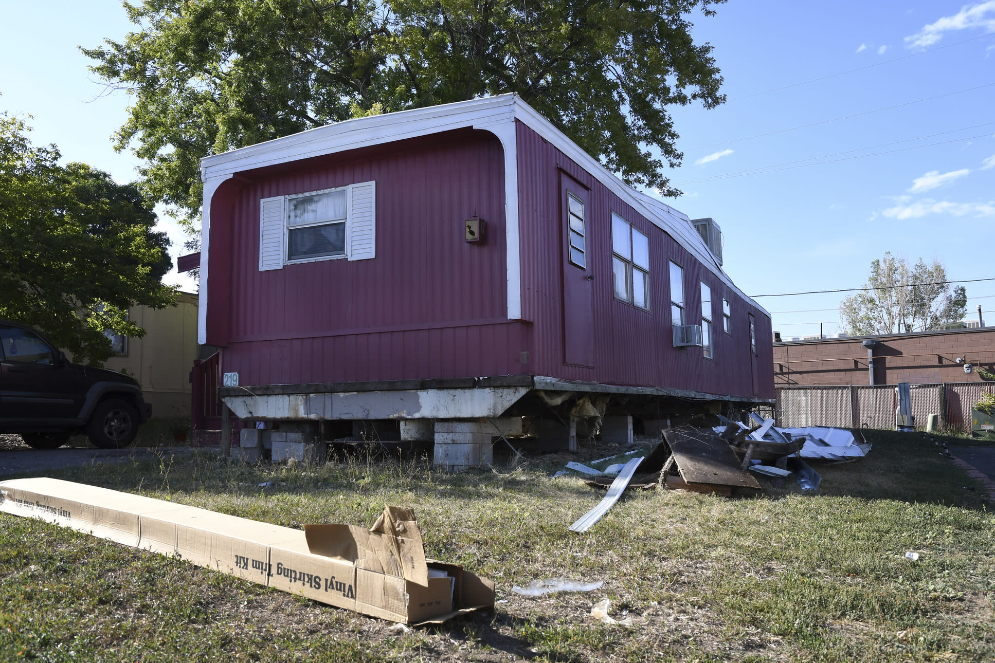ADVANCE ON THURSDAY, SEPT. 12 FOR USE ANY TIME AFTER 3:01 A.M. SUNDAY SEPT 15 - In this Aug. 30th 2019 photo shows a home sitting with a vinyl skirting kit in boxes on the ground, seemingly ready for replacement at Lamplighter Village, a manufactured and mobile home park in Federal Heights, Colo. Across Colorado, where the housing crisis impacts both rural and urban towns, the strife between mobile home park residents and park owners approaches a boiling point. The business model -- in which homeowners pay lot rent to park their houses on someone else's land -- capitalizes on the immobility and economic fragility of tenants who often can't afford to move or live anywhere else. (Kathryn Scott/The Colorado Sun)