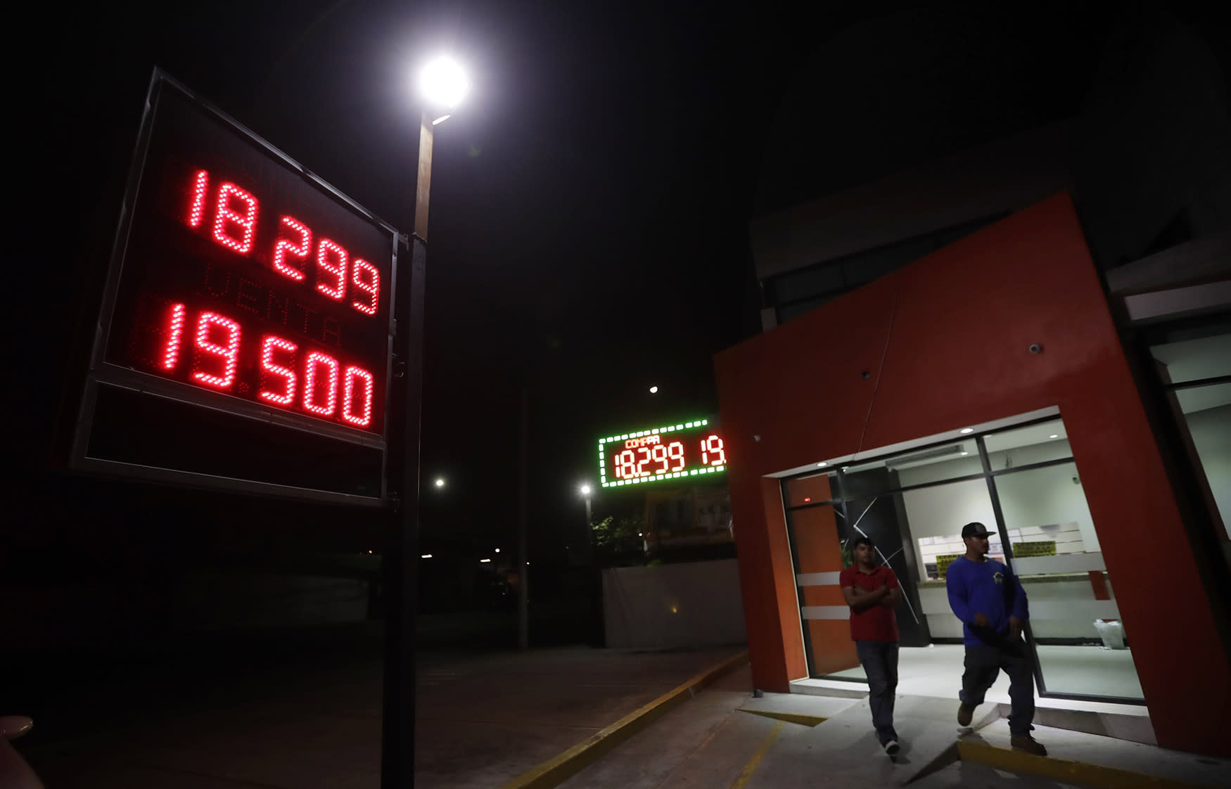<p>Men leave a currency exchange business displaying rates of the Mexican peso Tuesday, Nov. 8, 2016, in Tijuana, Mexico. The rising prospect of a Trump presidency jolted markets around the world Wednesday, sending Dow futures and Asian stock prices sharply lower as investors panicked over uncertainties on trade, immigration and geopolitical tensions. The Mexican peso likewise tumbled and investors looking for safe assets bid up the price of gold. (AP Photo/Gregory Bull) </p>