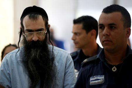 REFILE - CORRECTING TYPOYishai Schlissel (C), convicted of killing a woman during the 2015 Jerusalem Gay Pride Parade, is escorted by security personnel before he is sentenced at the Jerusalem District Court June 26, 2016. REUTERS/Ronen Zvulun