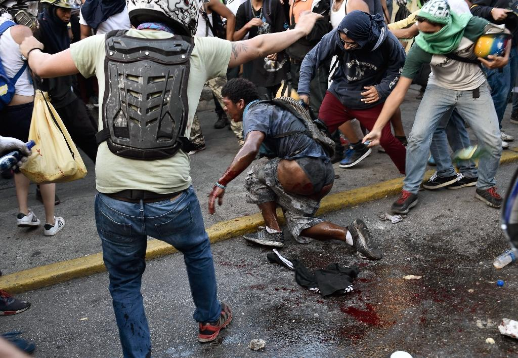 Venezuelan demonstrators pour petrol over an alleged thief during an opposition rally in Caracas (AFP Photo/CARLOS BECERRA)