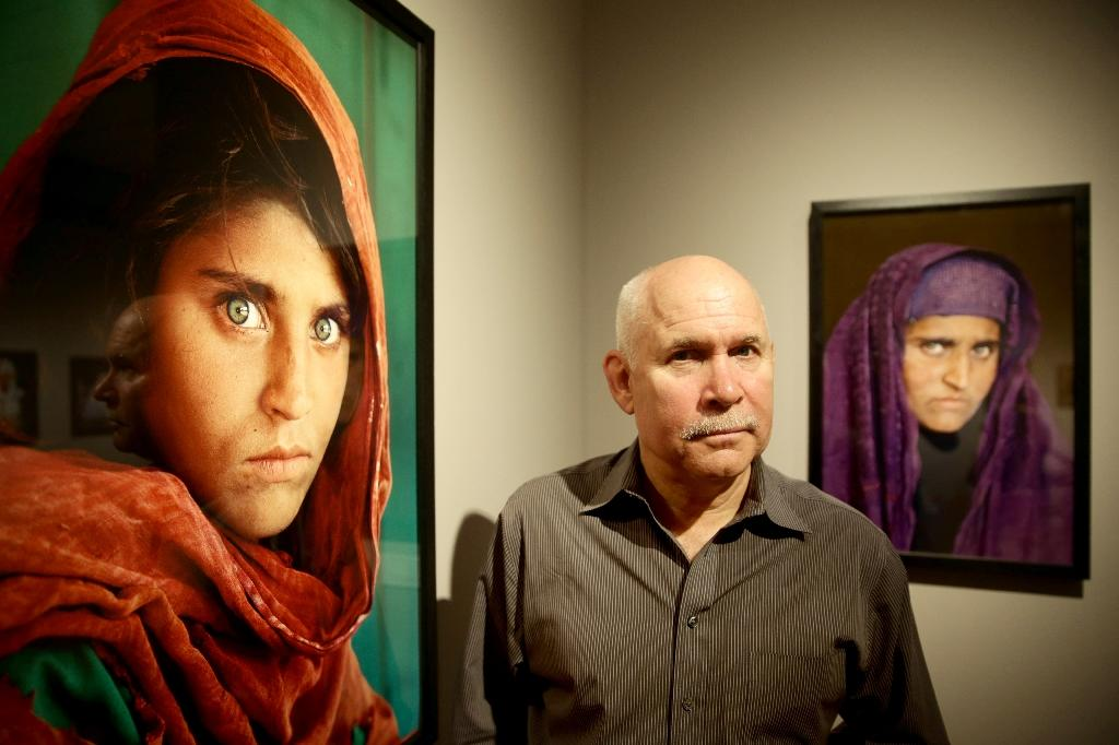 "US photographer Steve McCurry poses next to his photos of ""Afghan Girl"" Sharbat Gula at an exhibition of his work in Hamburg, Germany in June 2013"