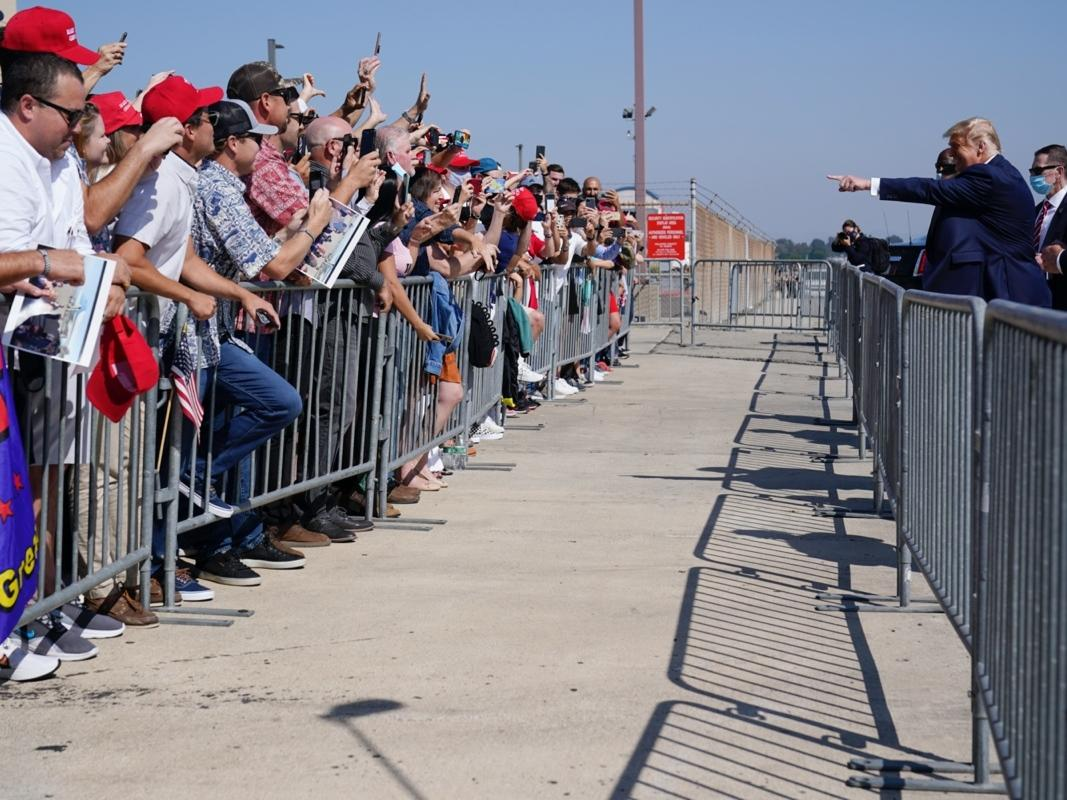 President Donald Trump greets supporters Sunday after stepping off Air Force One at John Wayne Airport in Santa Ana, Calif.