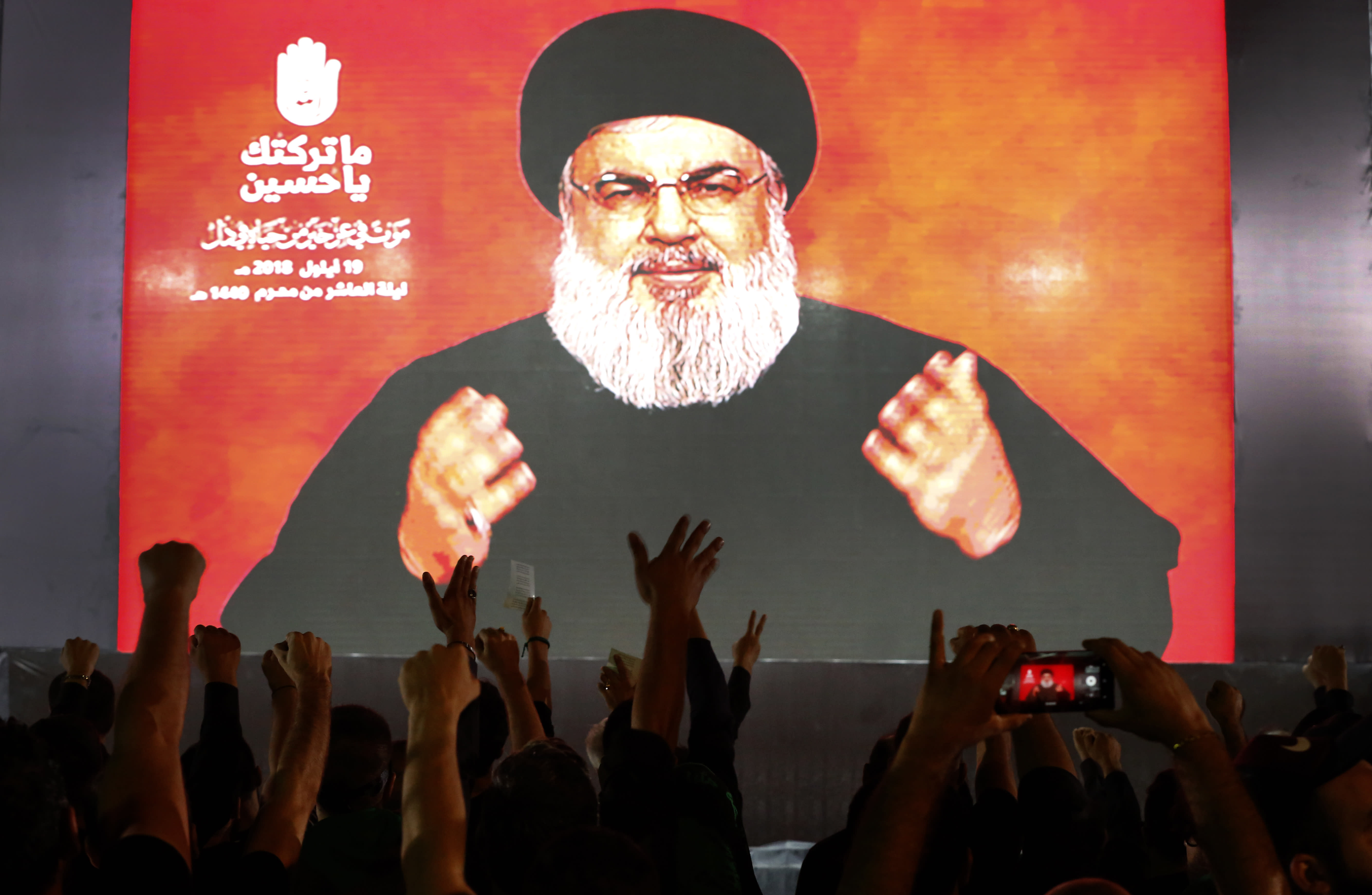 Hezbollah leader Sheik Hassan Nasrallah speaks via a video link, as his supporters raise their hands, during activities to mark the ninth of Ashura, a 10-day ritual commemorating the death of Imam Hussein, in a southern suburb of Beirut, Lebanon, Wednesday, Sept. 19, 2018. Hassan Nasrallah says his group may reduce the number of its fighters in Syria because of an easing of the conflict, particularly after a recent Russian-Turkey agreement that prevented an offensive on the last rebel stronghold. (AP Photo/Hussein Malla)