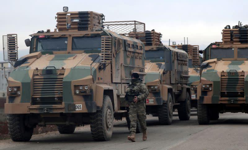 A Turkish soldier walks near Turkish military vehicles in Hazano near Idlib