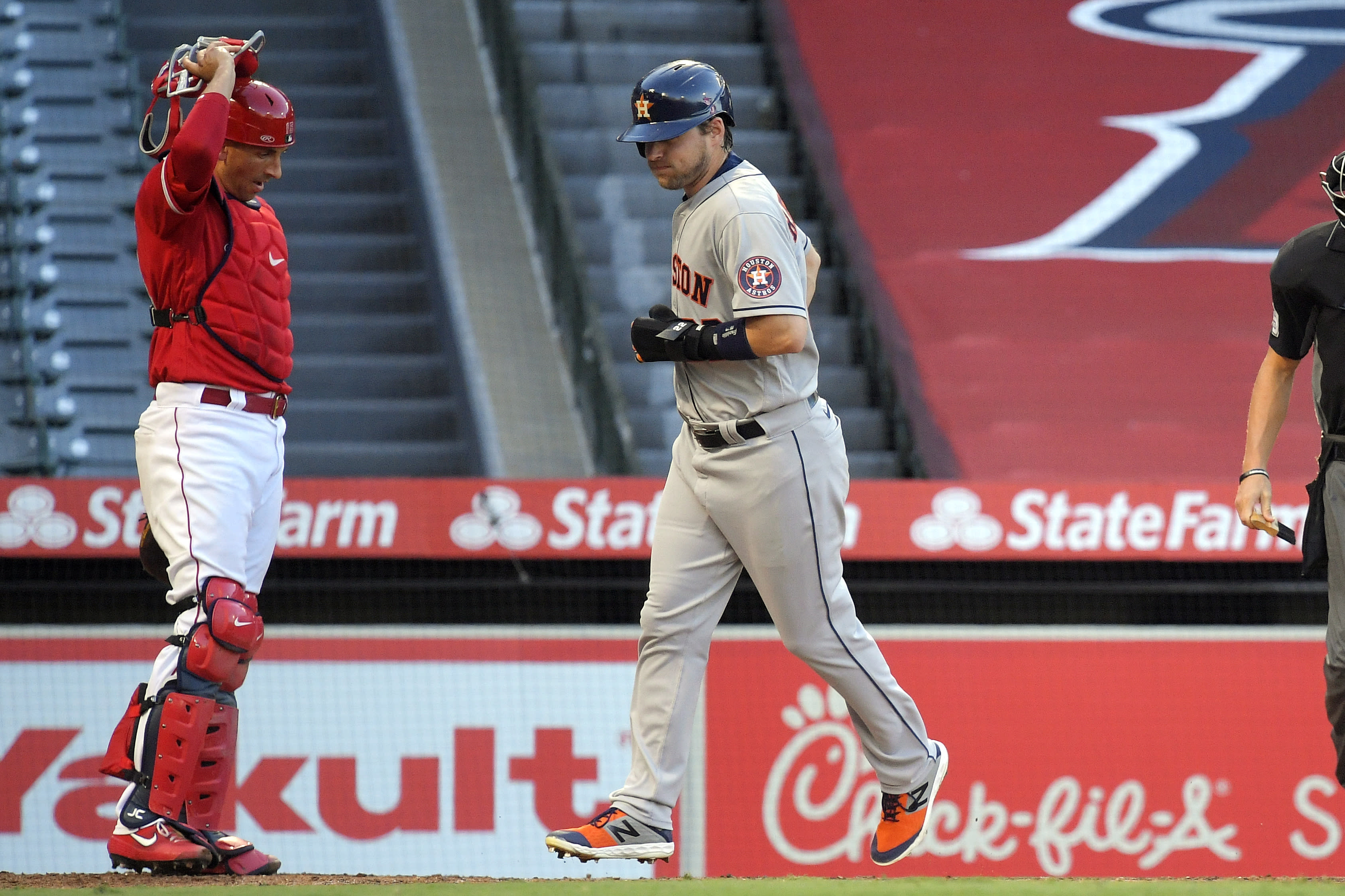 Houston Astros' Josh Reddick, right, scores as Los Angeles Angels catcher Jason Castro watches after George Springer was walked with the bases loaded during the second inning of a baseball game Friday, July 31, 2020, in Anaheim, Calif. (AP Photo/Mark J. Terrill)