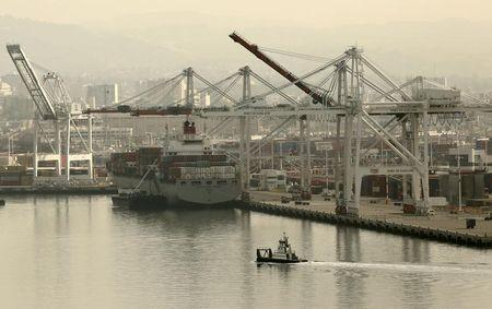 A tug boat passes in front of a freighter at the Port of Oakland in Oakland