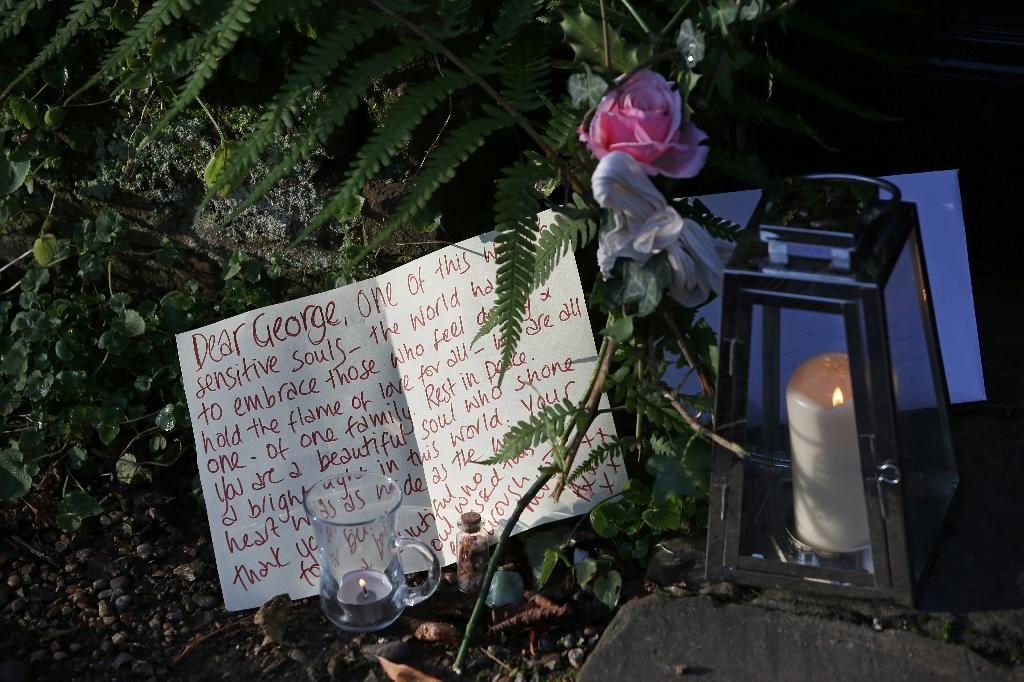A message of condolence is pictured beside candles and a single rose outside the north London home of British singer George Michael on December 26, 2016 (AFP Photo/Daniel Leal-Olivas)