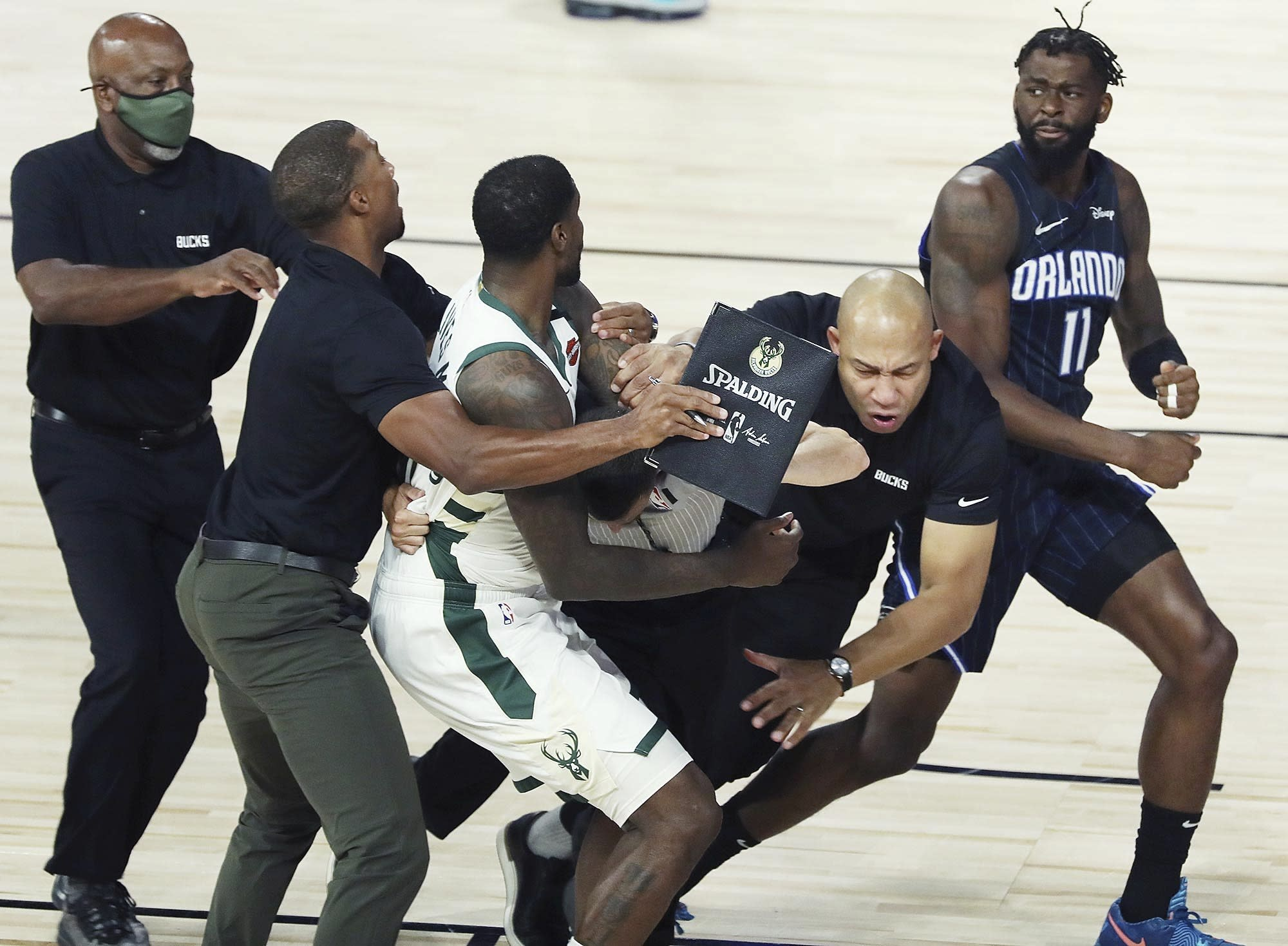 Milwaukee forward Marvin Williams (20) and Orlando forward James Ennis III (11) get into a skirmish as Milwaukee assistant coach Darvin Ham falls while breaking up the fight during Game 3 of an NBA basketball first-round playoff series, Saturday, Aug. 22, 2020, in Lake Buena Vista, Fla. 9Stephen M. Dowell/Orlando Sentinel via AP)