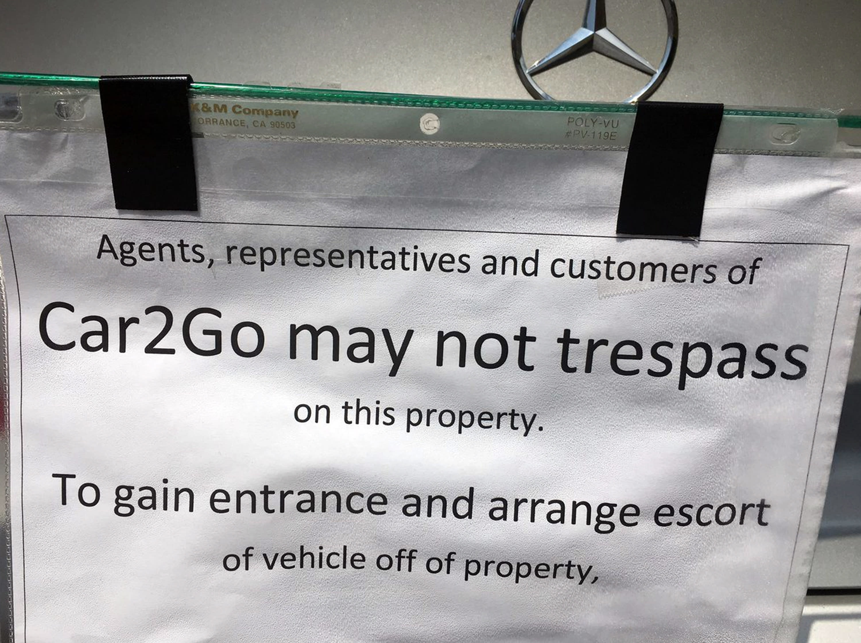 This undated photo provided by KOMO News shows a notice attached to a car-share vehicle parked at a Seattle duplex. Dan Smith took exception to the car2go Mercedes that has been parked there since May 17, 2019. He says he doesn't know who parked the car there, but it wasn't one of the tenants. By the next day he had erected the barricade, preventing other customers from using the vehicle. He wants Share Now, which operates car2go, to pay storage fees. The company says it won't tolerate having its vehicle held for ransom. (KOMO News via AP)