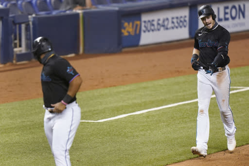 Miami Marlins' Brian Anderson, right, gestures to Jesus Aguilar as Aguilar waits for him to cross home plate after he hit a home run also scoring Aguilar and Garrett Cooper during the fifth inning of the second game of a baseball doubleheader against the Washington Nationals, Friday, Sept. 18, 2020, in Miami. (AP Photo/Wilfredo Lee)