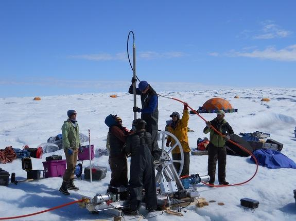 Sun on the Greenland Ice Sheet melts the ice surface, but a new study shows what happens next isn't the same across the ice sheet. In this photo, researchers align a borehole in Greenland.