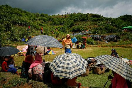 New Rohingya refugees sit on the ground as others clean bushes off of a hill to build makeshift shelters in Balukhali near Cox's Bazar, Bangladesh, September 2, 2017. REUTERS/Mohammad Ponir Hossain