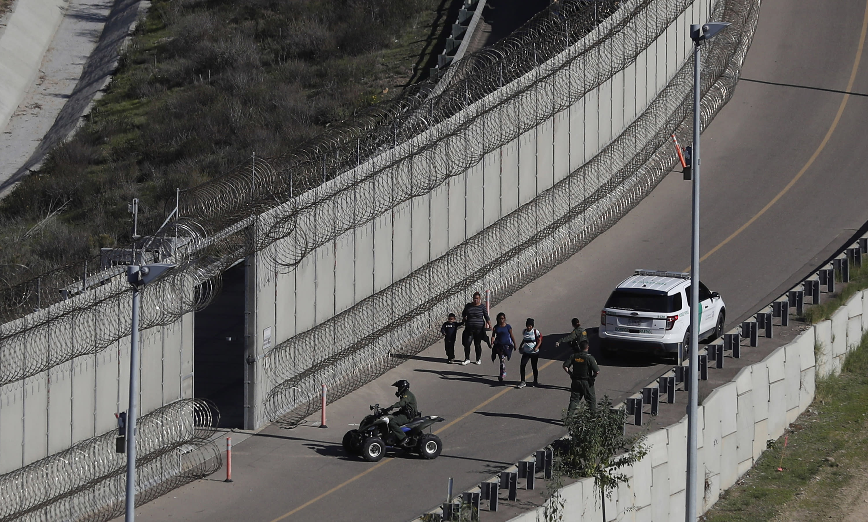 FILE - In this Dec. 16, 2018, file photo, Honduran asylum seekers are taken into custody by U.S. Border Patrol agents after the group crossed the U.S. border wall into San Diego, in this view from Tijuana, Mexico. In its efforts to remake the U.S. immigration system, the Trump administration has often stumbled over an obscure law that governs how administrative policies are made. Its latest test is a mammoth proposal to severely limit access to asylum, which invited nearly 80,000 public comments before the Wednesday, July 15, 2020, deadline to offer feedback. (AP Photo/Moises Castillo, File)
