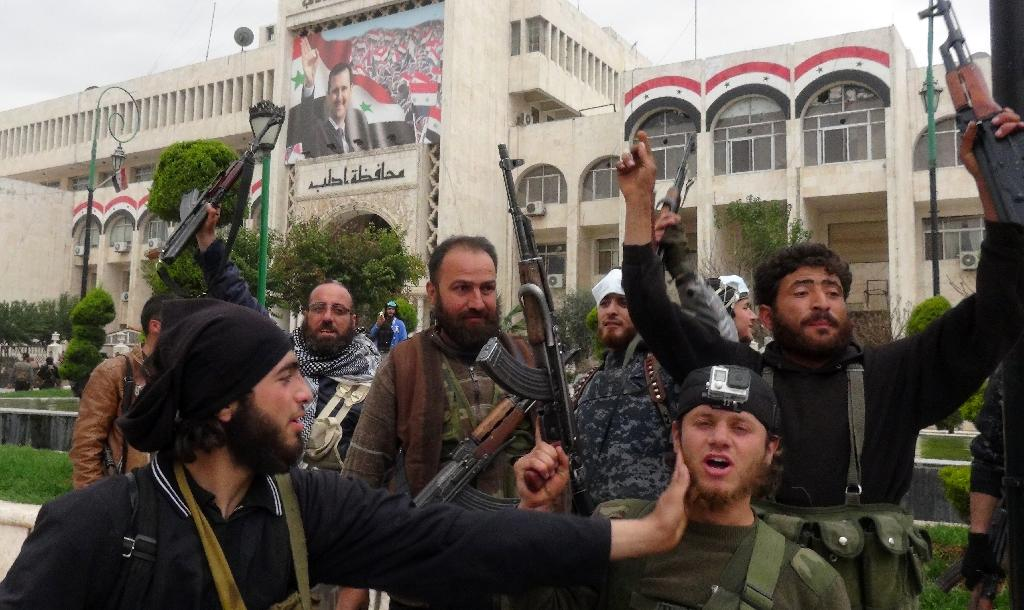 Fighters loyal to Al-Qaeda's Syrian affiliate and its allies gather outside the building of Idlib Governorate on March 28, 2015 in the northwestern Syrian city of Idlib (AFP Photo/Sami Ali)
