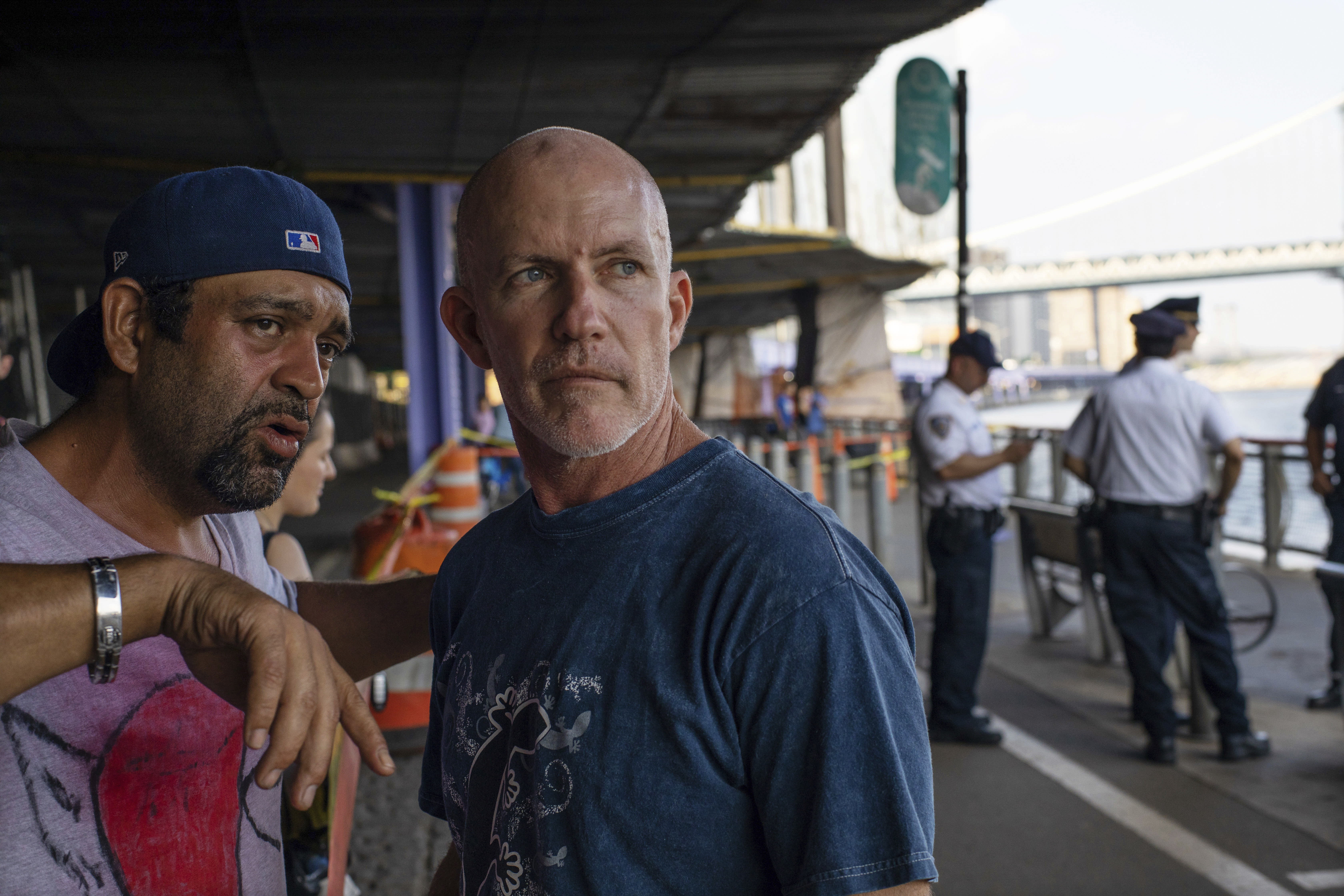 FILE - In this Aug. 5, 2018, file photo, Monte Campbell, of Stillwater, Okla., right, stands under the Brooklyn Bridge in the Manhattan borough after jumping into New York's East River to rescue a baby floating in the East River. A Bronx father hopped a plane to Thailand after carrying his dead 7-month-old baby around New York City in a backpack and tossing the boy's body into the river and other tourist hotspots, police said Wednesday. Campbell waded into shallow water, retrieved the baby and started CPR. (AP Photo/Robert Bumsted, File)