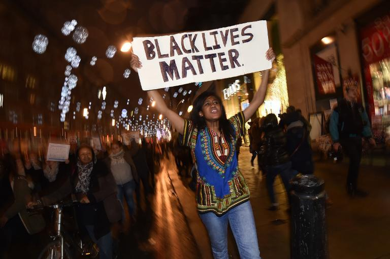 Demonstrators hold up placards and march down Oxford Street in central London on November 26, 2014 during a protest over the US court decision not to charge the policeman who killed unarmed black teenager Michael Brown (AFP Photo/Leon Neal)