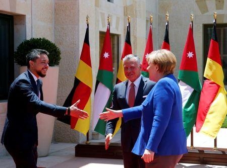 German Chancellor Angela Merkel shakes hands with Crown Prince Hussein at the Royal Palace in Amman, Jordan, June 21, 2018. REUTERS/Muhammad Hamed