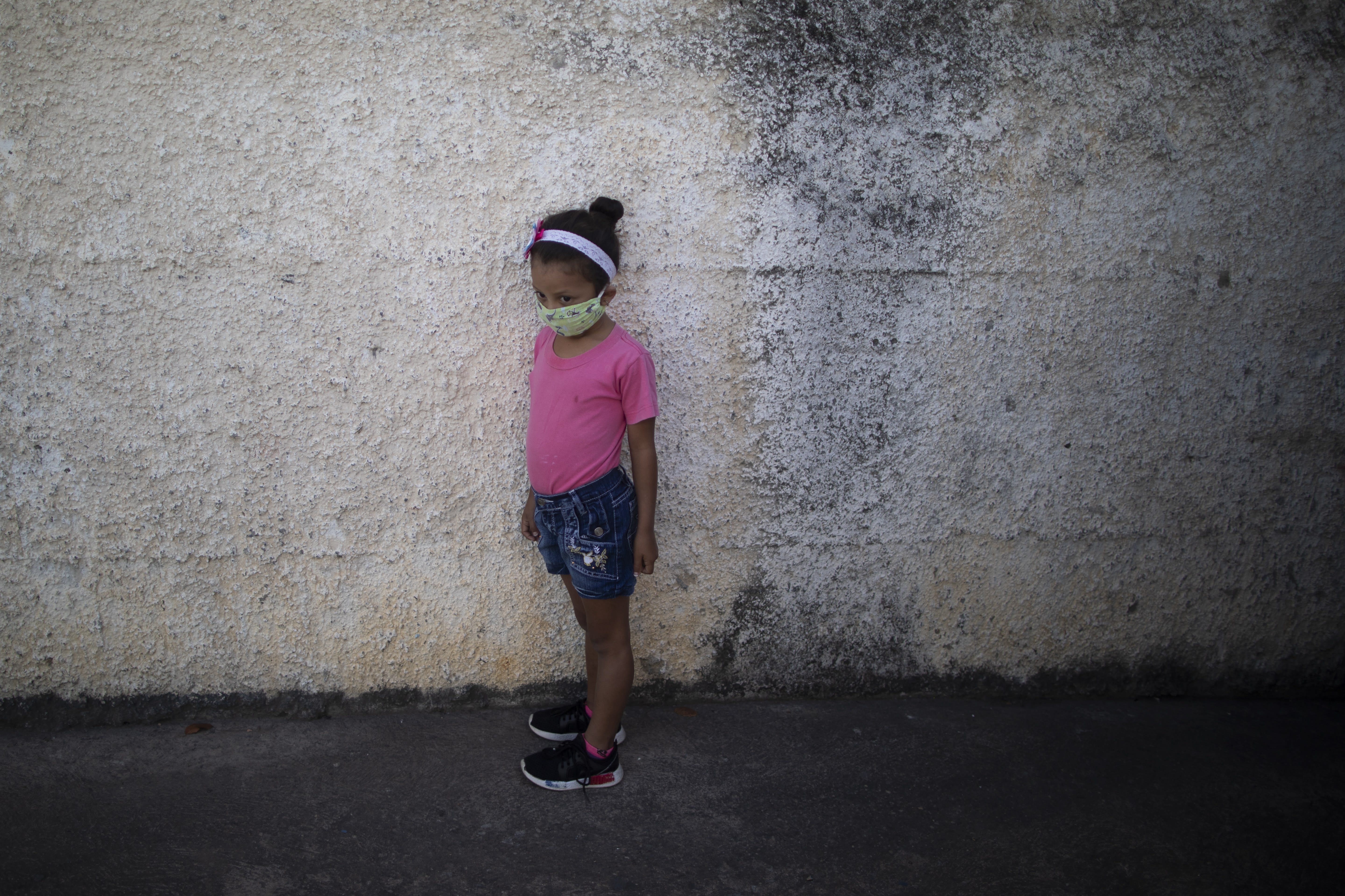 A girl wearing a mask to protect herself from the new coronavirus, waits at the entrance of the Fe y Alegria school as her mother drops off her homework, in Caracas, Venezuela, Tuesday, April 28, 2020. The schools uses Facebook and WhatsApp to send online homework assignments. (AP Photo/Ariana Cubillos)