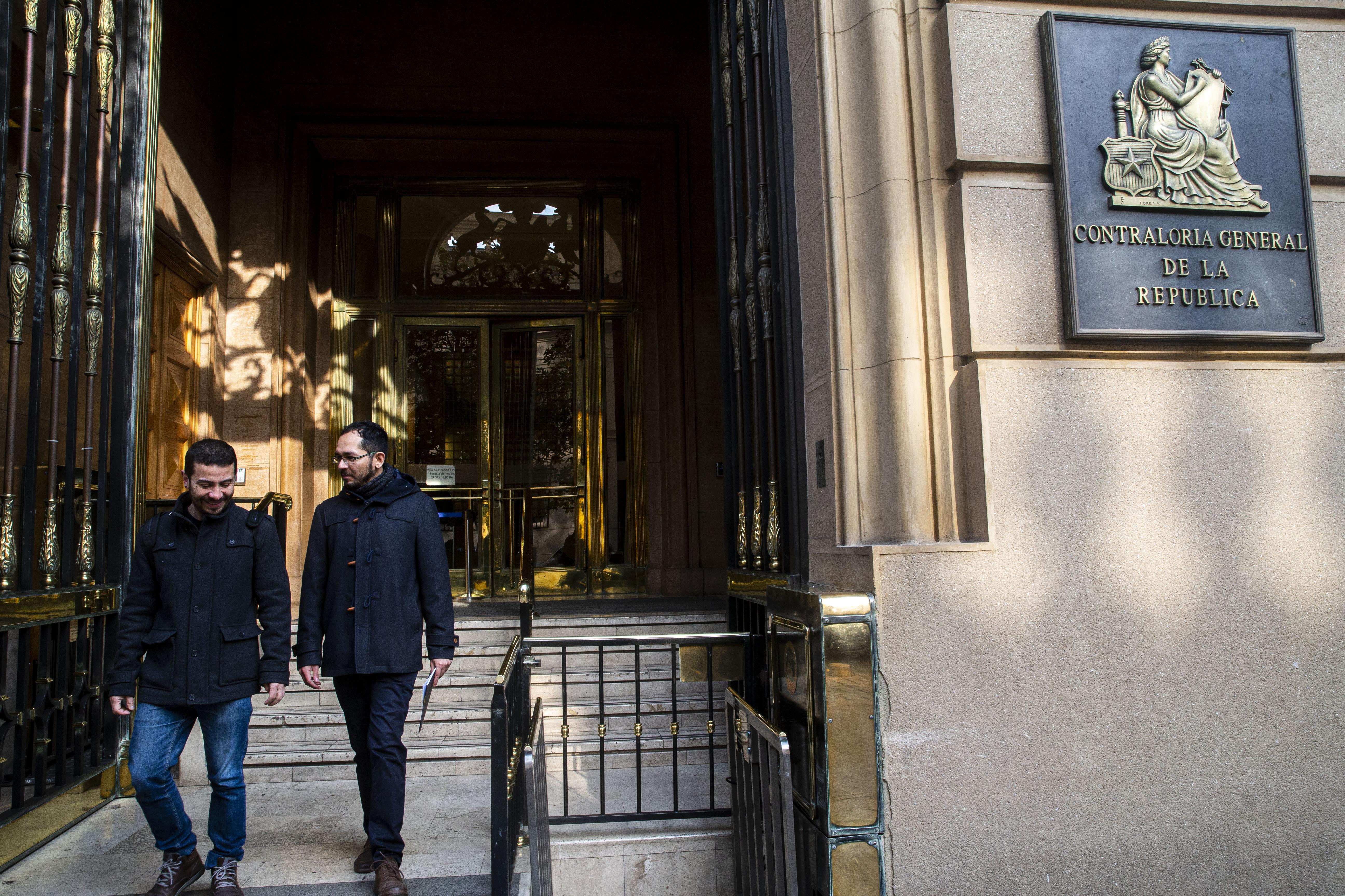 Gonzalo Velasquez, right, and Ramon Gomez, leaders of Chile's Homosexual Integration and Liberation Movement, leave the comptroller general office after presenting an accusation against the government for breaching a same-sex marriage agreement in 2016 with the Inter-American Commission on Human Rights in Santiago, Chile, Tuesday, Sept. 10, 2019. Two groups have formally asked the South American country's controller-general to require President Sebastián Piñera's government to promote a measure in congress to legalize same-sex marriage. (AP Photo/Esteban Felix)