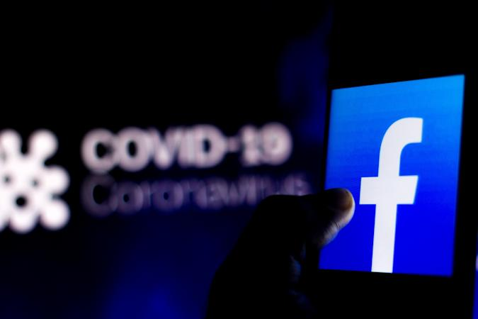 BRAZIL - 2020/04/05: In this photo illustration the Facebook logo seen displayed on a smartphone with a computer model of the COVID-19 coronavirus in the background. (Photo Illustration by Rafael Henrique/SOPA Images/LightRocket via Getty Images)