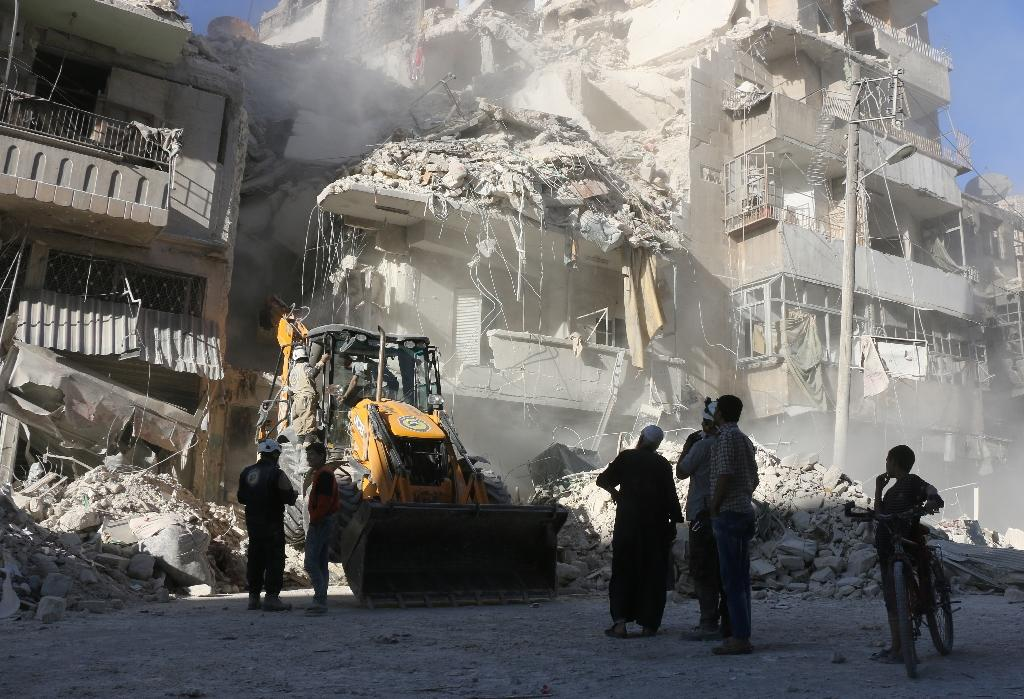 A tractor clears the rubble following airstrikes by the Syrian regime in the rebel held neighbourhood of Tariq a-Bab in Aleppo on September 24, 2016 (AFP Photo/Thaer Mohammed)