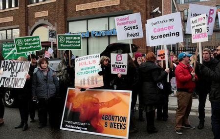 Anti-abortion activists (L) rally next to supporters of Planned Parenthood outside a Planned Parenthood clinic in Detroit, Michigan, U.S. February 11, 2017. REUTERS/Rebecca Cook