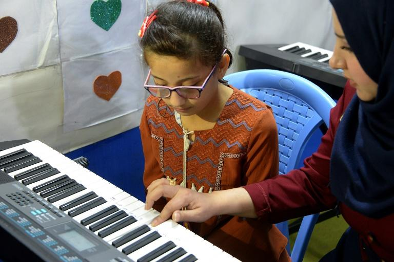 A girl with special needs practises a short eight-note tune to improve her motor skills at a private rehabilitation centre in Mosul