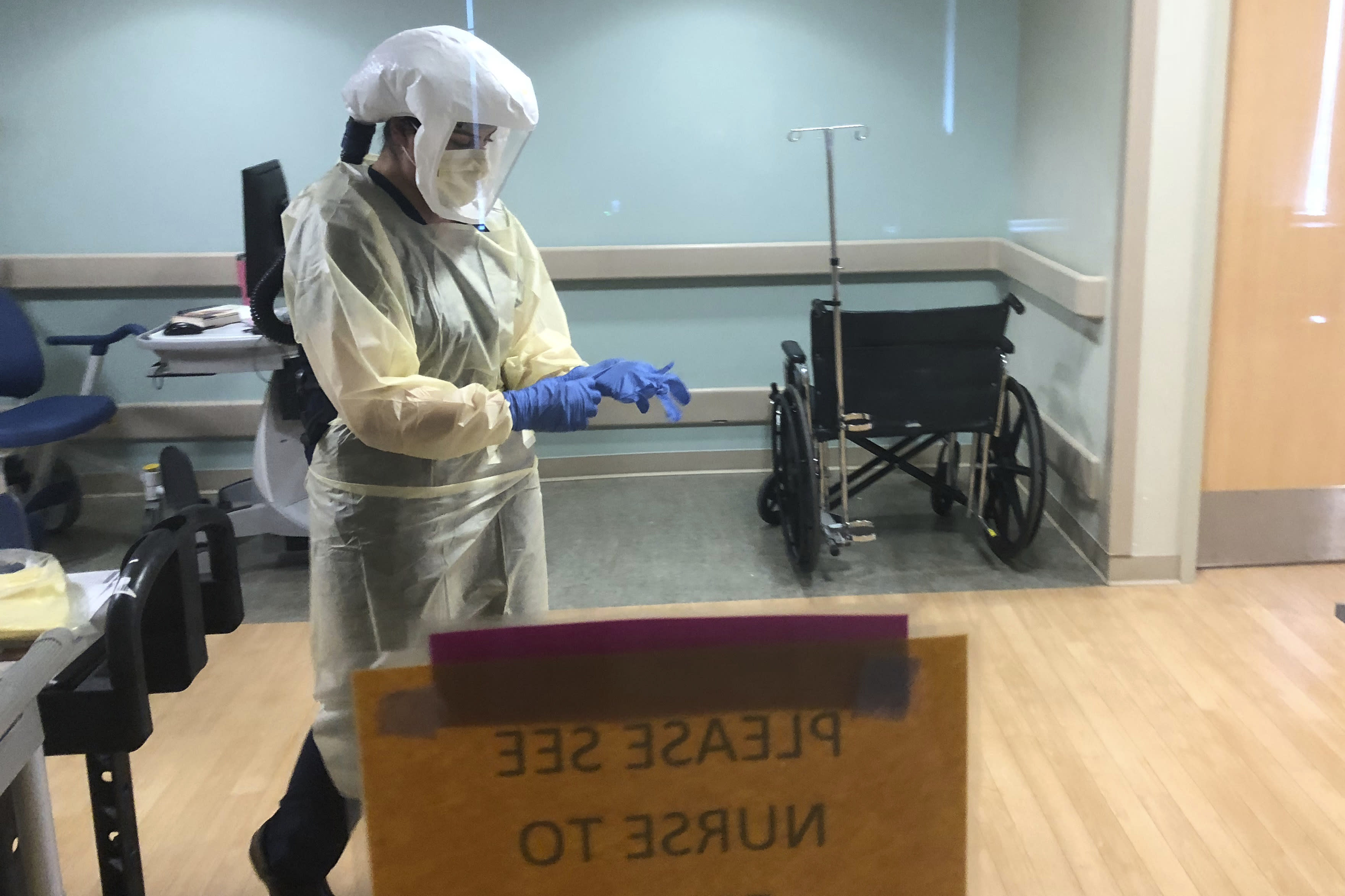 In this photo provided by the UPMC, Dr. Ruba Nicola, chairwoman of family medicine at UPMC East, adjusts her personal protective equipment at the UPMC East hospital in Monroeville, Pa., on April 17, 2020. The University of Pittsburgh Medical Center's 40 hospitals in Pennsylvania, New York, Maryland and Ohio joined a study underway in the United Kingdom, Australia and New Zealand that randomly assigns patients to one of dozens of possible treatments and uses artificial intelligence to adapt treatments, based on the results. (UPMC via AP)