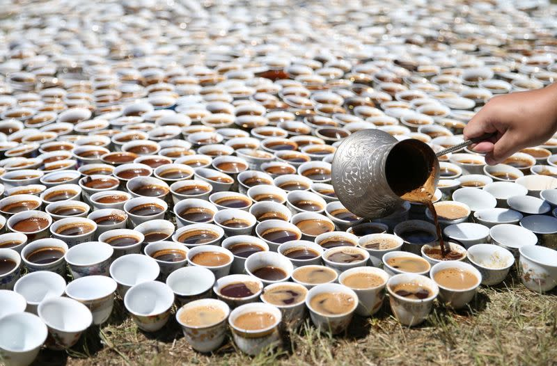A volunteer prepares the installation of some 8,000 traditional porcelain cups filled with Bosnian coffee at the Potocari-Srebrenica Memorial Centre for victims of the 1995 massacre of some 8,000 Muslim men and boys