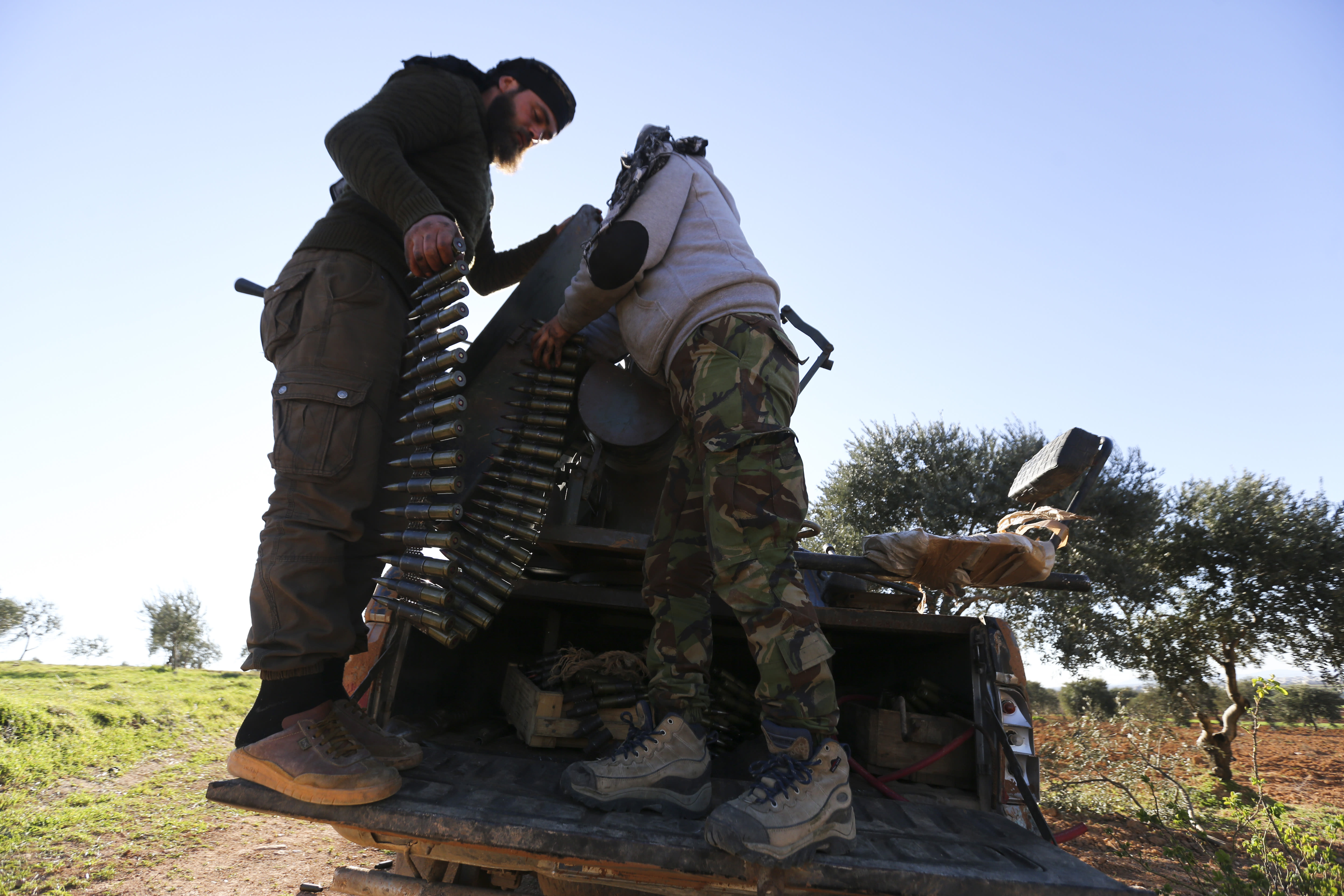 Turkish backed Syrian fighters load ammunition at a frontline near the town of Saraqib in Idlib province, Syria, Wednesday, Feb. 26, 2020. Syrian government forces have captured dozens of villages, including major rebel strongholds, over the past few days in the last opposition-held area in the country's northwest. (AP Photo/Ghaith Alsayed)