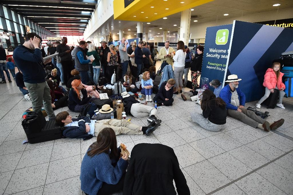 Passengers wait at the North Terminal at London Gatwick Airport,as police frantically searched for the operators of the drones that had forced the suspension of all flights (AFP Photo/Glyn KIRK )