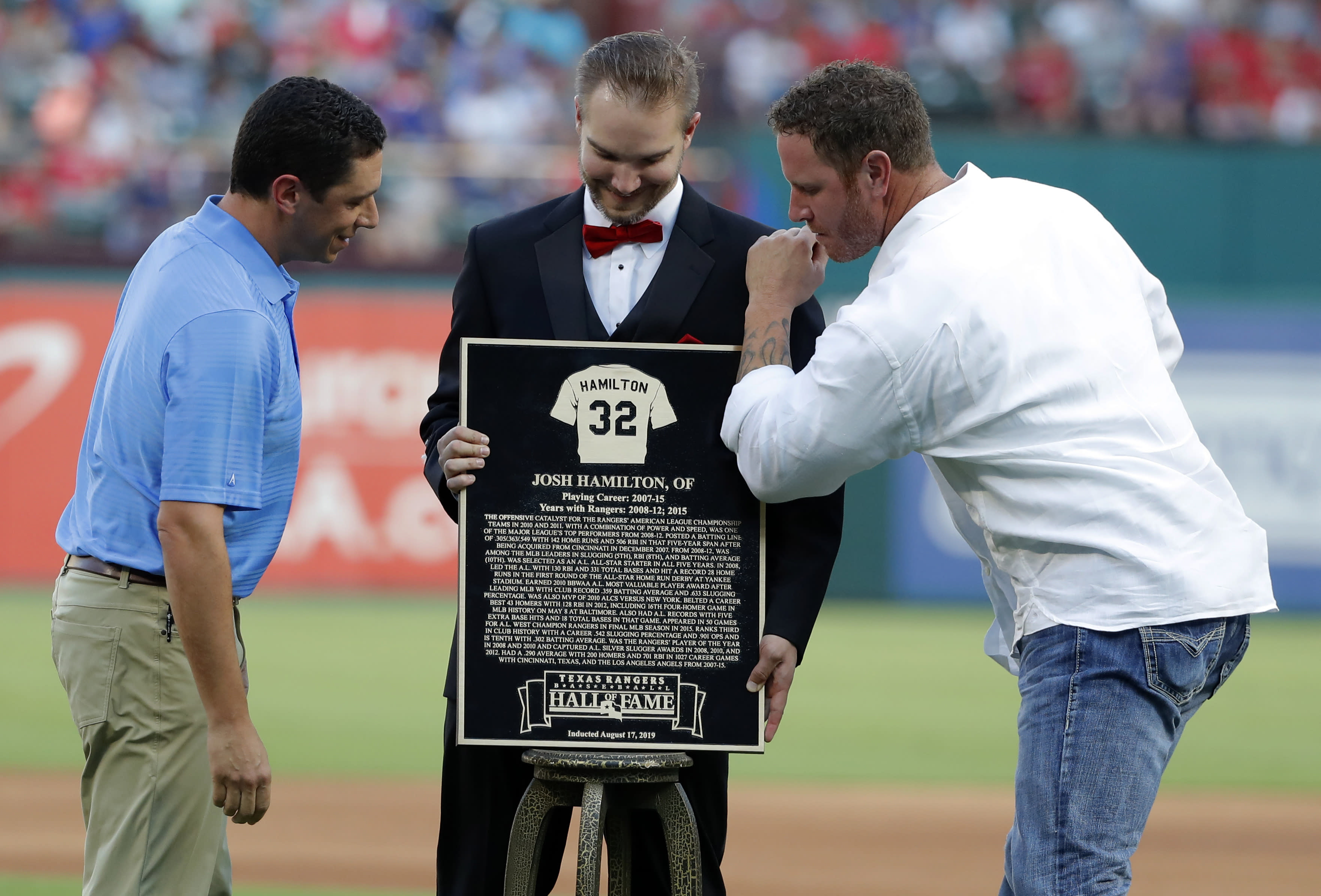 Texas Rangers general manager Jon Daniels smiles as former player Josh Hamilton, right, pretends to put a shine on a plaque presented to him during a club Hall of Fame ceremony before the team's baseball game against the Minnesota Twins in Arlington, Texas, Saturday, Aug. 17, 2019. (AP Photo/Tony Gutierrez)