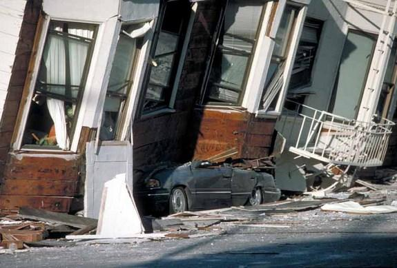 A car crushed under the third story of an apartment building in the Marina district.