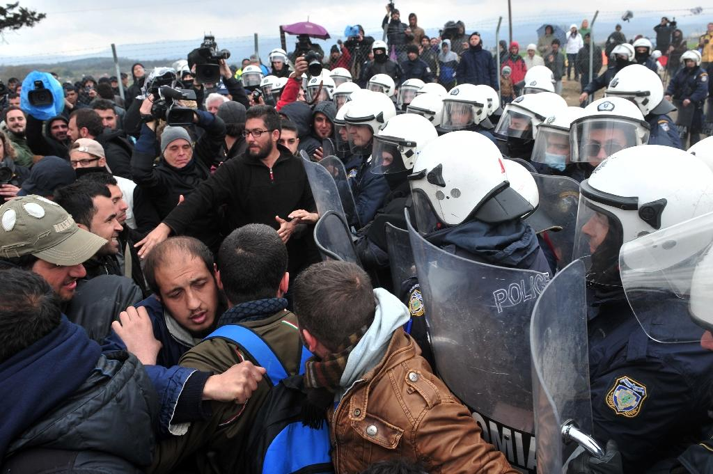 Migrants protest in front of anti-riot police at the makeshift camp near the Greek village of Idomeni on the Greek-Macedonian border on March 27, 2016, where thousands of refugees and migrants are stranded (AFP Photo/Sakis Mitrolidis)