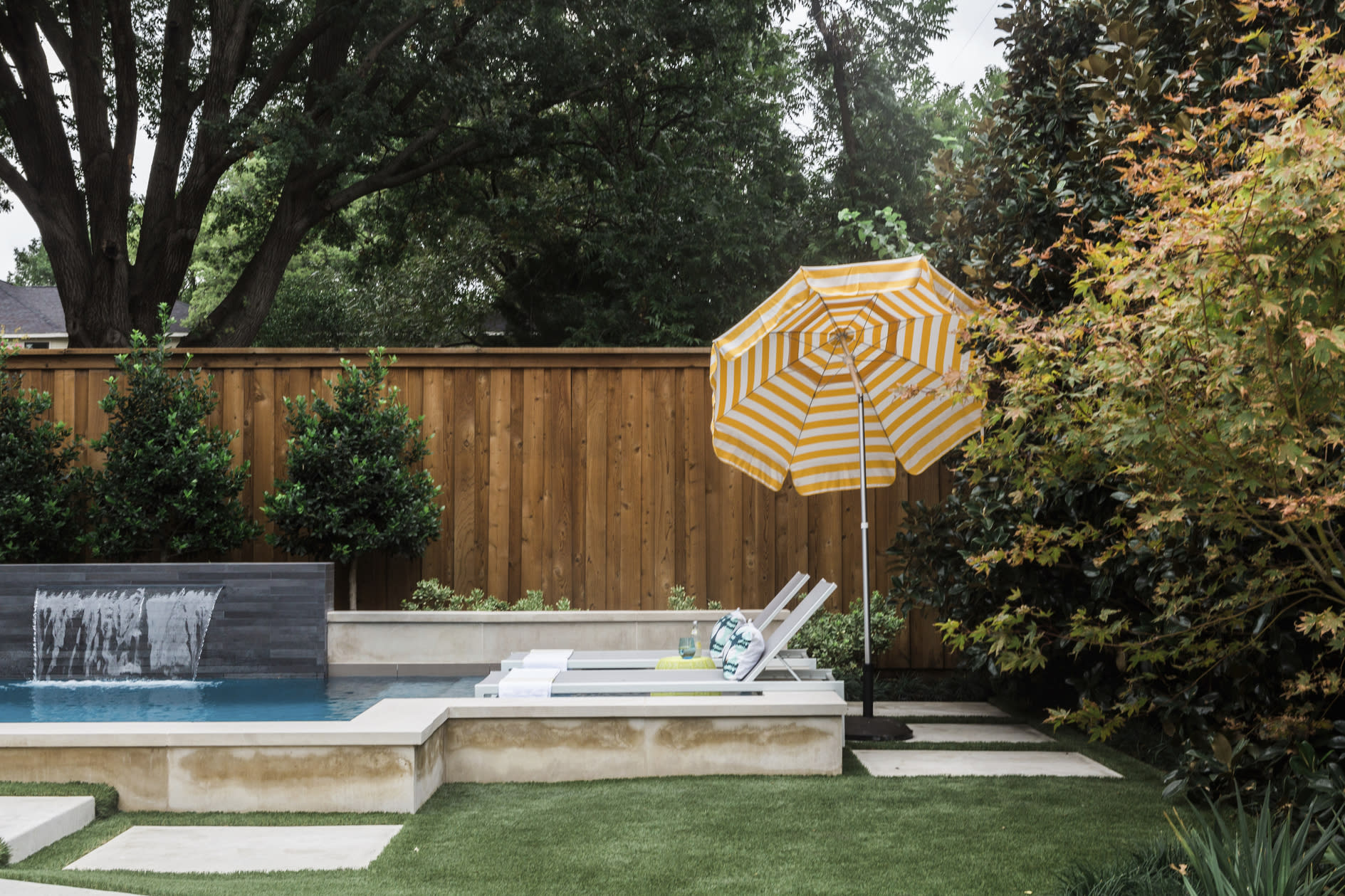 This undated photo shows a home in Texas' backyard area designed by Abbe Fenimore, founder of Studio Ten 25. The seating around backyard swimming pools is often located in direct sunlight, so Fenimore suggests using large, durable and easily positioned umbrellas to allow guests to control their sun exposure. (Heather Hawkins/Abbe Fenimore via AP)