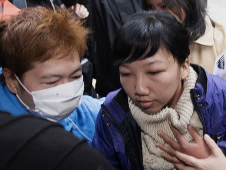 Former Indonesian domestic helper Erwiana Sulistyaningsih (R) is helped to enter a district court in Hong Kong December 8, 2014. REUTERS/Stringer