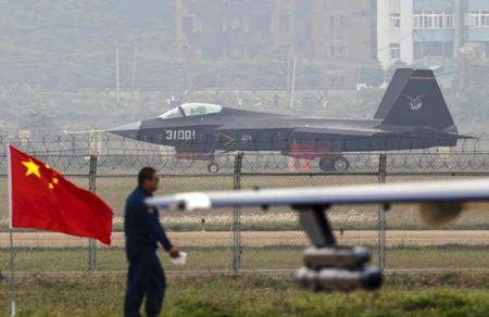 A J-31 stealth fighter (background) of the Chinese People's Liberation Army Air Force lands on a runway after a flying performance at the 10th China International Aviation and Aerospace Exhibition in Zhuhai, Guangdong province, in this November 11, 2014 file photo. REUTERS/Alex Lee/Files