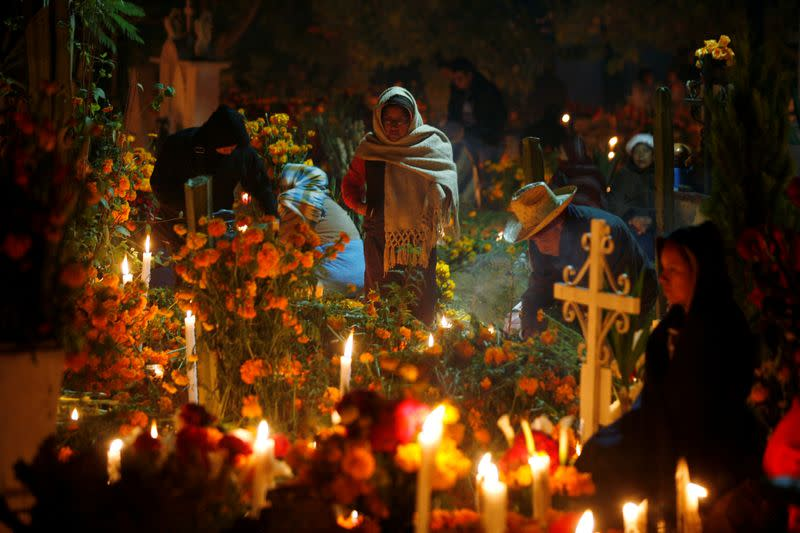 FILE PHOTO: Indigenous people are seen by the graves of their relatives during an annual Day of the Dead celebration, in Santa Maria Atzompa